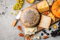 Various types of cheese. On wooden cutting board, top view royalty free stock images
