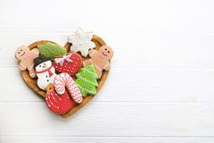 Various types of Christmas decorative gingerbread cookies on wooden heart shaped plate on white table top view, text space Stock Image