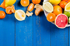 Various types of citrus fruit on a blue painted wooden background. Top view Royalty Free Stock Photo