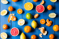 Various types of citrus fruit on a blue painted wooden background Royalty Free Stock Photos