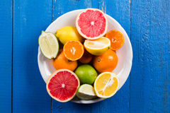 Various types of citrus fruit on a blue painted wooden background. Top view Stock Photo