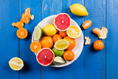 Various types of citrus fruit on a blue painted wooden background. Top view Royalty Free Stock Photos
