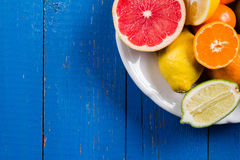 Various types of citrus fruit on a blue painted wooden background. Top view Royalty Free Stock Image