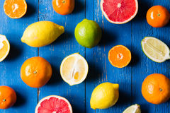 Various types of citrus fruit on a blue painted wooden background. Top view Royalty Free Stock Images