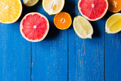 Various types of citrus fruit on a blue painted wooden background. Top view Stock Photos