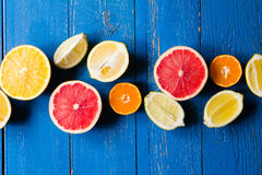 Various types of citrus fruit on a blue painted wooden background Royalty Free Stock Photo