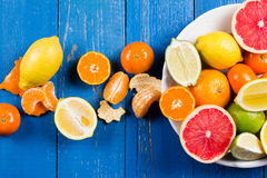 Various types of citrus fruit on a blue painted wooden background. Top view Stock Images