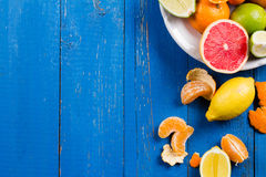 Various types of citrus fruit on a blue painted wooden background. Top view Stock Image