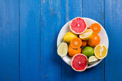 Various types of citrus fruit on a blue painted wooden background. Top view Royalty Free Stock Photography