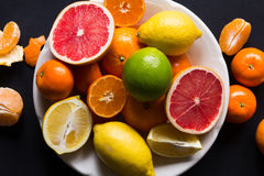 Various types of citrus fruit on a dark background. Top view Stock Images