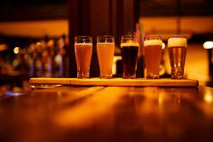 Various types of craft beer in small glasses on a wooden table in a pub. stock photography