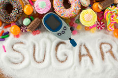 Various types of doughnuts and cupcakes with glucometer stock images
