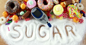 Various types of doughnuts and cupcakes with glucometer. On wooden table stock video