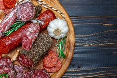 Various types of Dried organic salami sausage on wooden cutting board royalty free stock photos