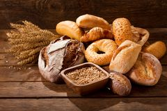 Fresh baked bread with wheat ears. Various types of fresh baked bread with wheat ears on wooden table stock photos