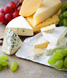 Various types of fresh Cheese with grapes on slate Stock Images