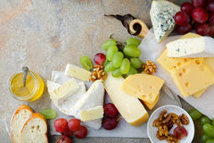 Various types of fresh Cheeses with grapes, honey, bread and walnuts on slate background Royalty Free Stock Images