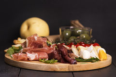 Various types of italian appetizers: ham, cheese, grissini, olives, fruits Royalty Free Stock Image