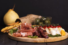 Various types of italian appetizers: ham, cheese, grissini, olives, fruits Royalty Free Stock Images