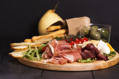 Various types of italian appetizers: ham, cheese, grissini, olives, fruits Royalty Free Stock Photo
