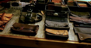 Various types of leather bag on table. In workshop stock video