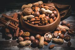 Various types of nuts and cinnamon sticks in a wooden bowl on a dark background. Low key lighting royalty free stock photo