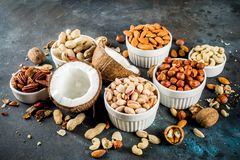 Various types of nuts. Walnuts, pecans, peanuts, hazelnuts, coconut, almonds, cashews, in bowls, on a dark blue concrete table top view stock photography