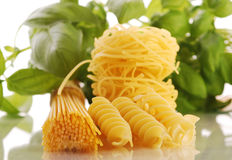 Various types of pasta with basil and tomatoes Stock Images