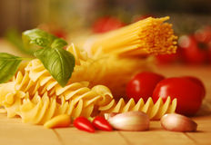 Various types of pasta with basil and tomatoes Stock Image
