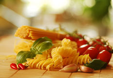 Various types of pasta with basil and tomatoes Stock Photography