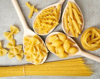 Various types of pasta on grey background, from above Stock Photography