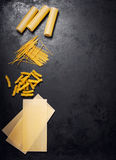 Various types of pasta - lasagna, fussili, spaghetti and cannell. Oni on a dark background. View from above with copy space Stock Photos