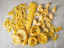 Various types of pasta on stone table, from above Stock Image