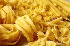 Various types of pasta on stone table Stock Photos