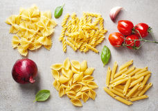 Various types of pasta and vegetables on grey stone table, top v Stock Image