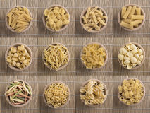 Various types of raw pasta in a wooden bowl Royalty Free Stock Photos