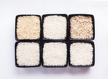 Various types of rice. Various types of white and gray rice in black bowls on white Stock Image