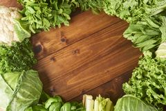 Various types of salad leaves and cabbage on wooden background. royalty free stock photo