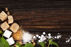 Various types of sugar from above on wooden table.