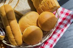Various types of tasty breads on the table. Various types of tasty breads in a basket with table cloth above wooden table Royalty Free Stock Photo