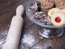 Various types of tasty cookies on glass tray next to a roller on wooden table. Royalty Free Stock Photography