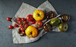 Various types of tomatoes on a linen fabric. Flat lay royalty free stock photography