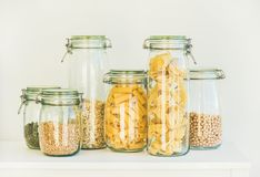 Uncooked cereals, grains, beans and pasta for healthy cooking. Various uncooked cereals, grains, beans and pasta for healthy cooking in glass jars on kitchen Stock Photo