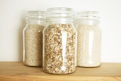 Various uncooked cereals, grains, and pasta for healthy cooking in glass jars on wooden table. Top view. Clean eating, balanced di. Various uncooked cereals stock photos