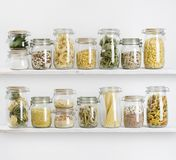 Various uncooked groceries in glass jars arranged on wooden shelves royalty free stock photos