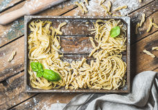 Various uncooked Italian pasta in wooden tray with basil leaves Stock Image