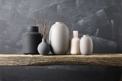 Various vases on wooden shelf. Home decor - various neutral colored vases with wood sticks on rough distressed wooden shelf against grey wall royalty free stock photo
