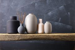 Various vases on wooden shelf. Home decor - various neutral colored vases with wood sticks on rough distressed wooden shelf against grey wall royalty free stock images