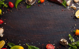 Various vegetables and herbs on dark wood table royalty free stock photos