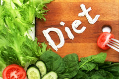 Various vegetables Lettuce frize, spinach and vegetables beautifully laid out near cutting board with word inscription diet, writt Stock Image
